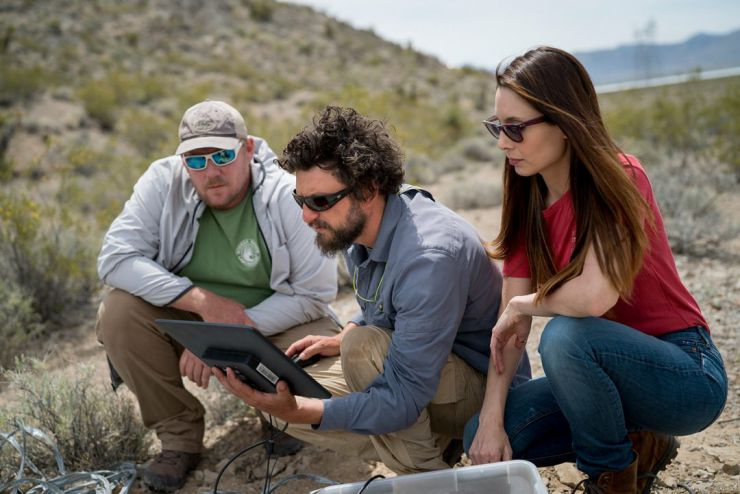 Steve Grodsky, center, a UC Davis postdoctoral scholar, checks camera traps set up to monitor interactions between animals and the Mojave milkweed in the Mojave Desert. Grodsky is part of AridLab, run by UC Davis professor Rebecca R. Hernandez, pictured r
